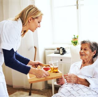 caregiver giving meal to old woman