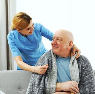 caregiver putting blanket around old man