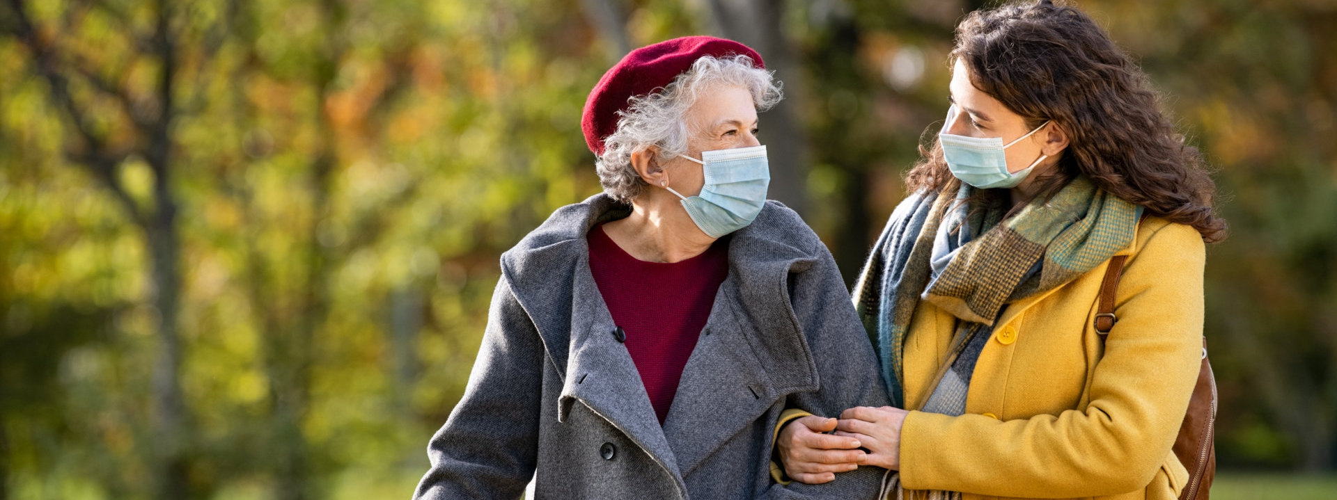 caregiver and old woman walking at the park